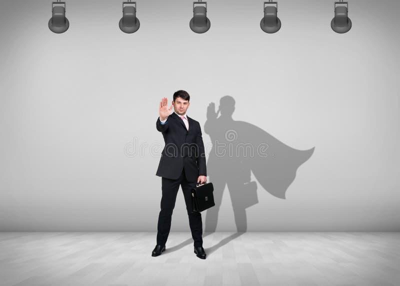 El hombre de negocios se coloca con la sombra en la pared imagenes de archivo