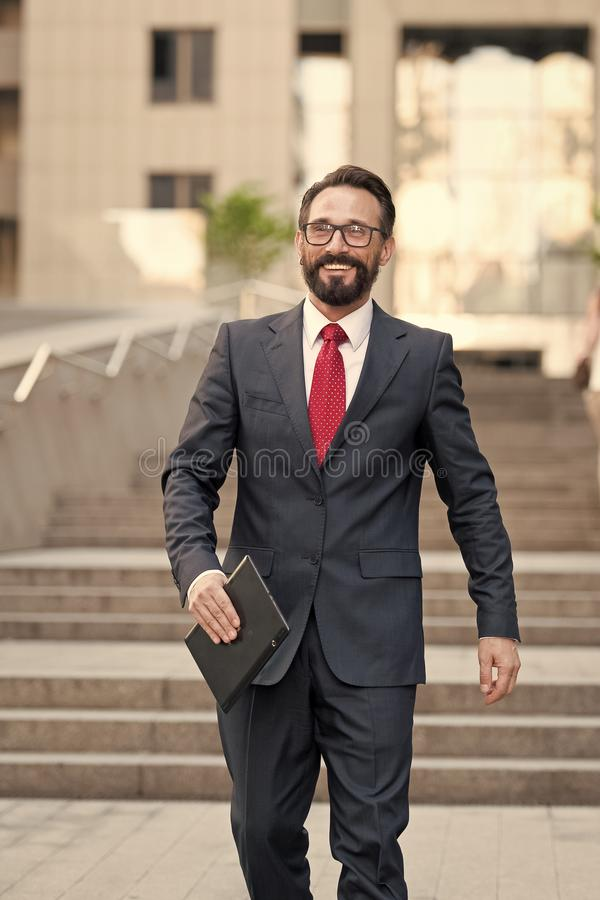 El hombre de negocios se coloca en el edificio de oficinas con la tableta a disposición la persona vestida en traje de negocios y fotografía de archivo