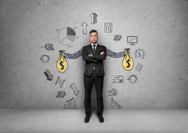 El hombre de negocios se coloca sobre fondo con las manos pintadas que sostienen bolsos del dinero rodeados por los gráficos econ fotografía de archivo libre de regalías
