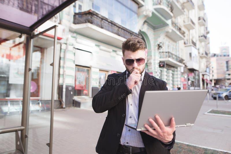 el hombre de negocios se está colocando afuera y está mirando un ordenador portátil Trabajo sobre el ordenador en el aire abierto imagen de archivo libre de regalías