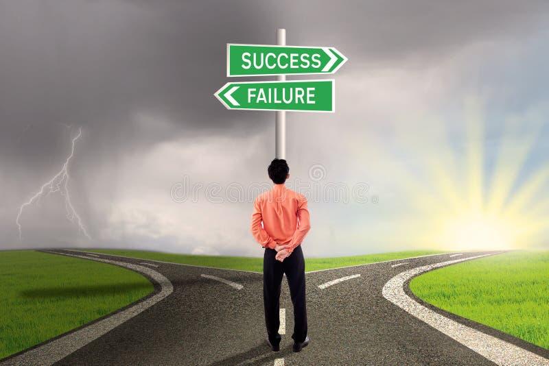 Hombre de negocios que elige el camino del éxito o del fracaso imagenes de archivo
