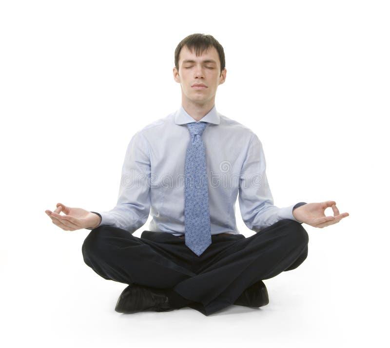 El hombre de negocios se está sentando en la posición de la yoga fotografía de archivo libre de regalías