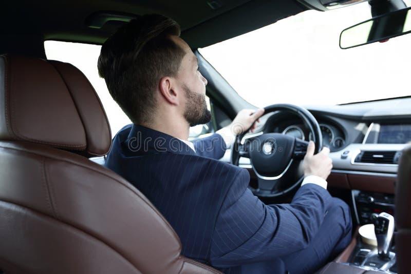 El hombre de negocios se sienta en la rueda en su coche y mira el camino foto de archivo