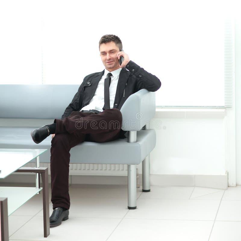 El hombre de negocios se sienta en el pasillo de la oficina y de hablar en un smartphone fotos de archivo