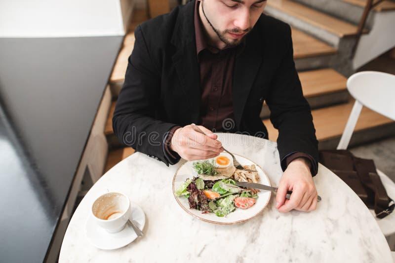El hombre de negocios se sienta en un restaurante acogedor y come una comida sana, ensalada, una taza de café que se coloca en la foto de archivo