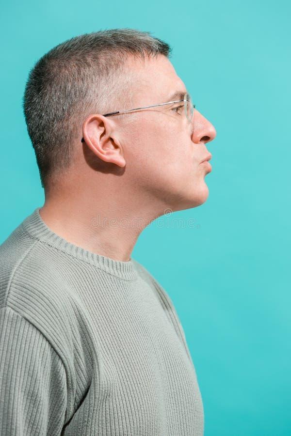 El hombre de negocios serio que se opone y que mira la cámara contra fondo azul fotografía de archivo libre de regalías