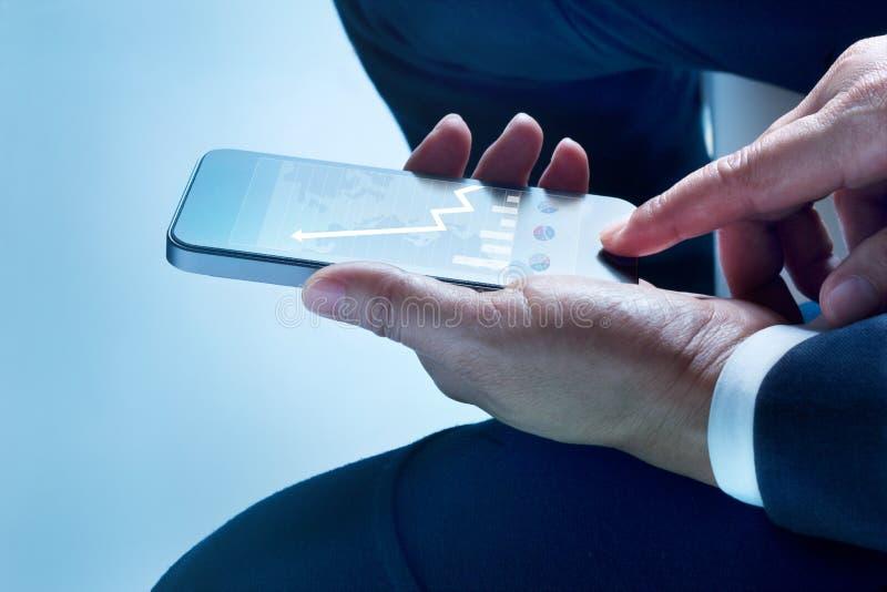 El hombre de negocios sienta el gráfico y las estadísticas del teléfono móvil de la pantalla táctil que suben en la pantalla imagenes de archivo