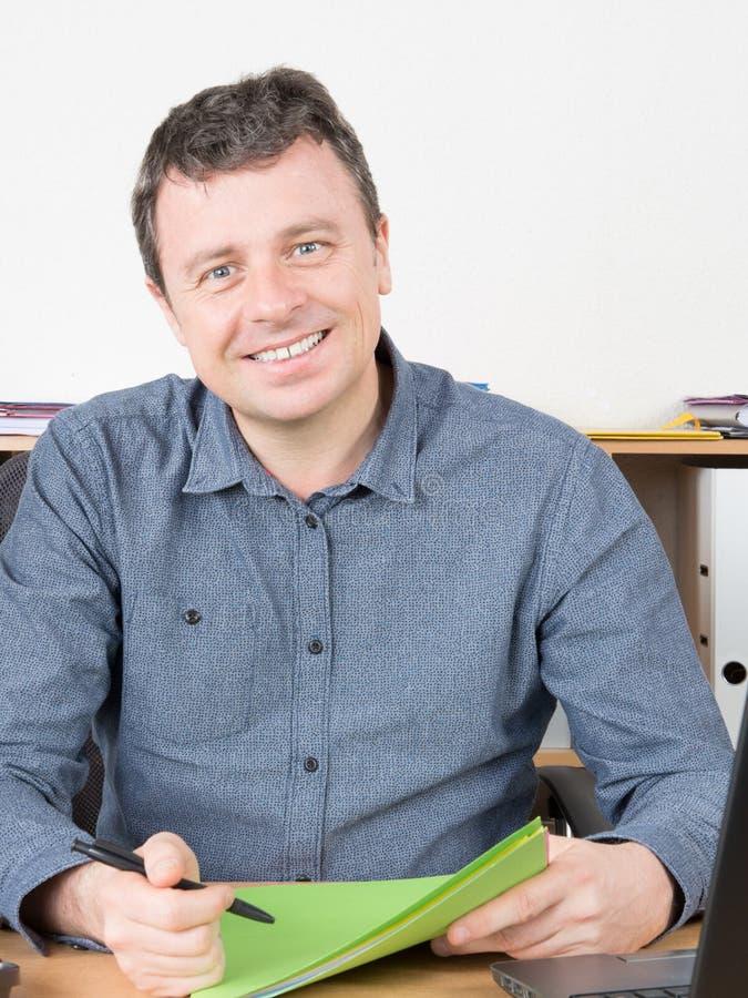 El hombre de negocios sonriente casual se sienta en el escritorio de la tabla de la oficina imágenes de archivo libres de regalías