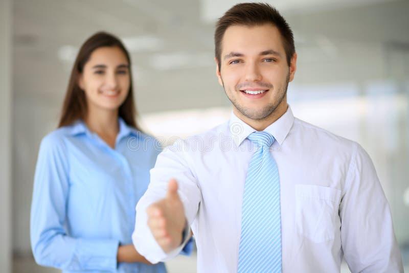 El hombre de negocios sonriente en oficina está listo para sacudir las manos fotografía de archivo