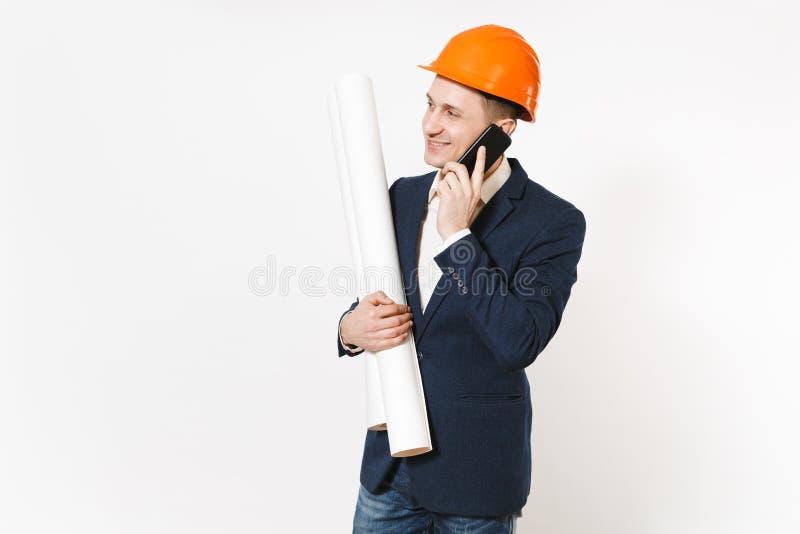El hombre de negocios sonriente joven en traje oscuro, casco de protección protector lleva a cabo los planes de los modelos, nego fotos de archivo
