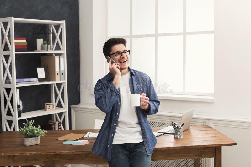El hombre de negocios sonriente joven tiene charla móvil foto de archivo libre de regalías