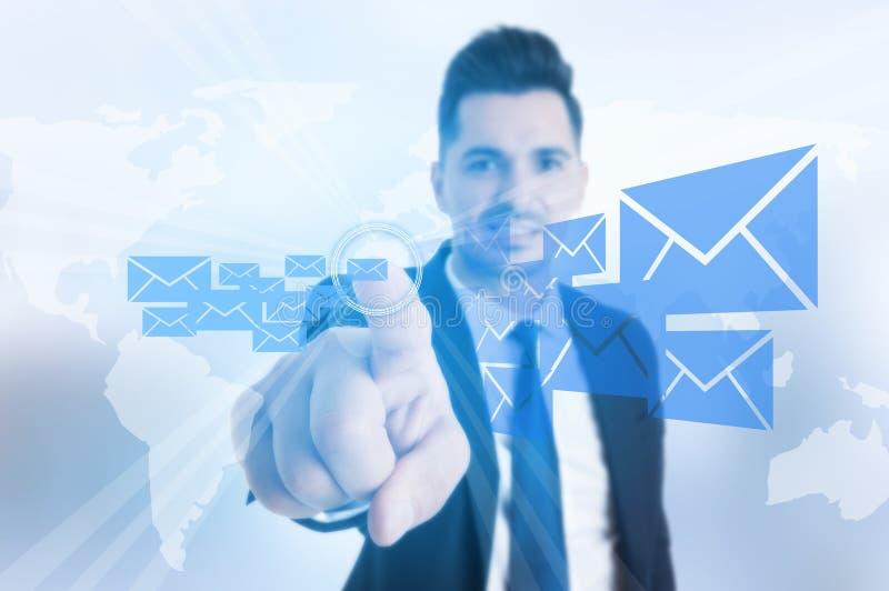 El hombre de negocios sonriente que presiona el mensaje o el correo electrónico abotona imagen de archivo libre de regalías
