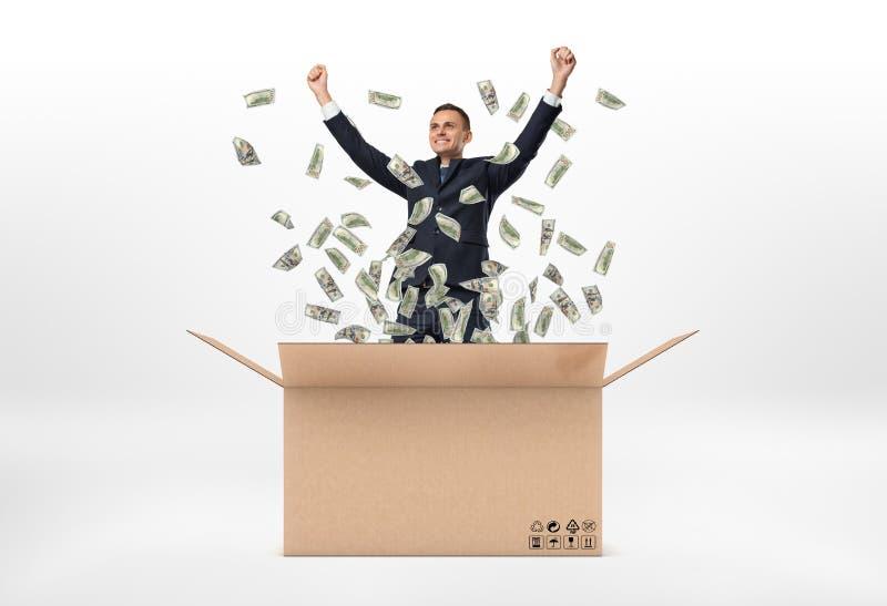 El hombre de negocios sonriente que se coloca en buzón grande abierto de la cartulina y los billetes de dólar se están cayendo al imagen de archivo libre de regalías