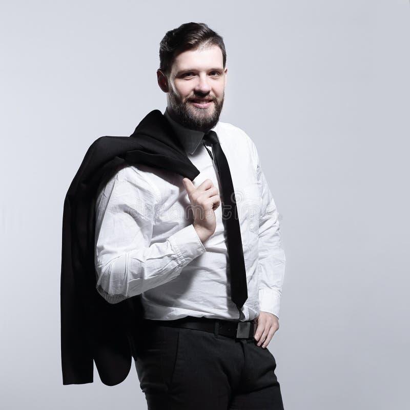 El hombre de negocios sonriente que sostiene una chaqueta sobre su hombro y endereza el lazo fotografía de archivo