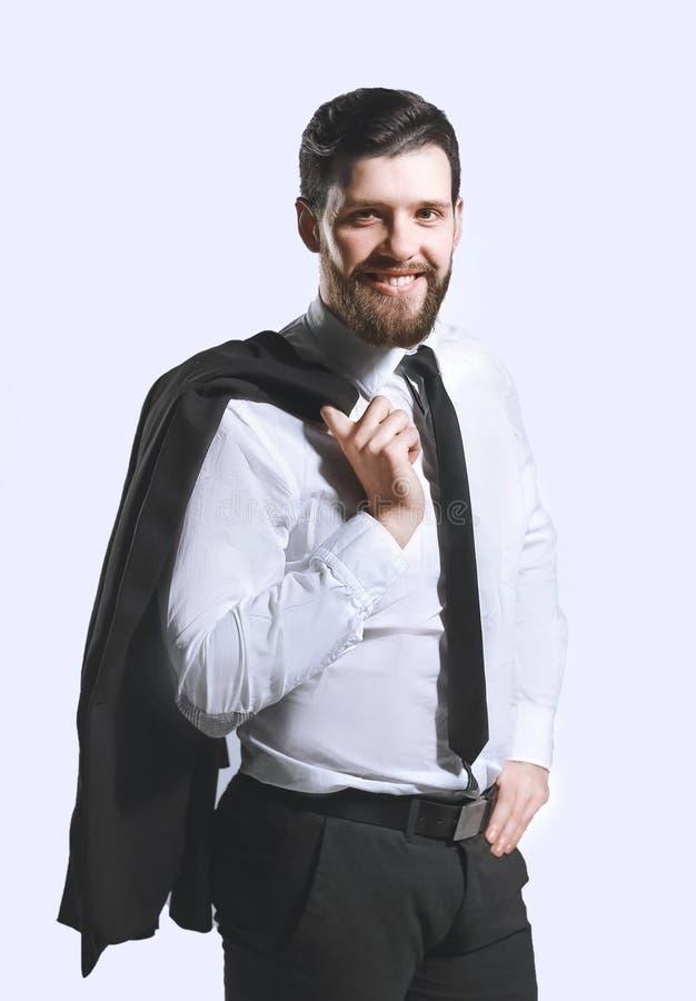 El hombre de negocios sonriente que sostiene una chaqueta sobre su hombro y endereza el lazo imagenes de archivo