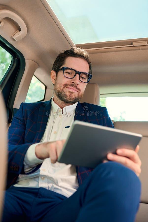El hombre de negocios sonriente usando una tableta durante su mañana conmuta fotografía de archivo
