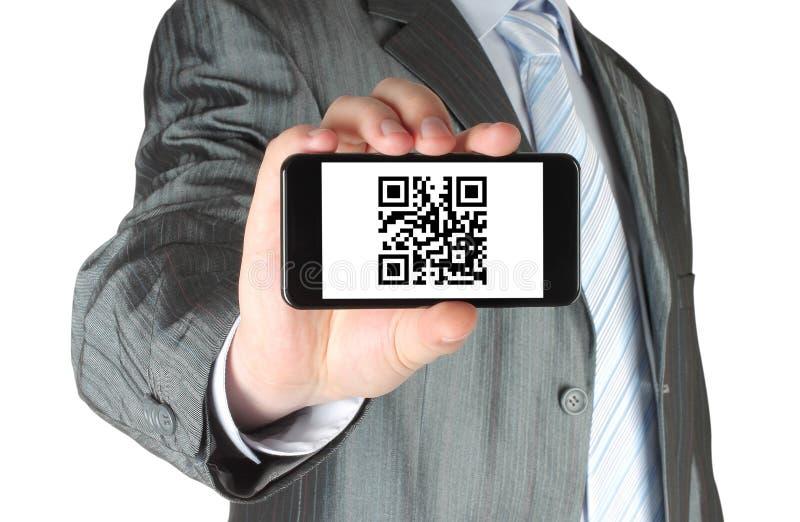 El hombre de negocios sostiene el teléfono elegante con código de QR imágenes de archivo libres de regalías
