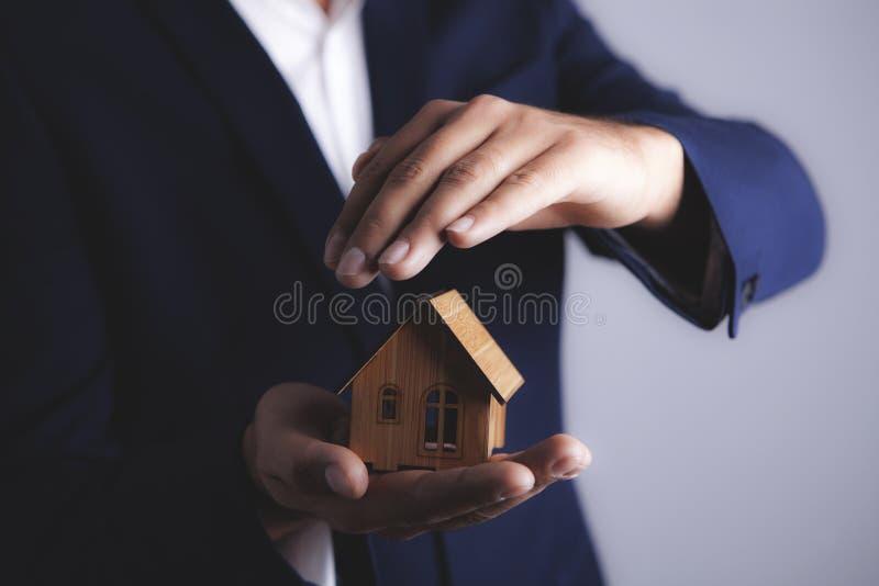 El hombre de negocios sostiene la casa fotografía de archivo