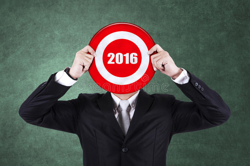 El hombre de negocios sostiene la diana con los números 2016 imagen de archivo