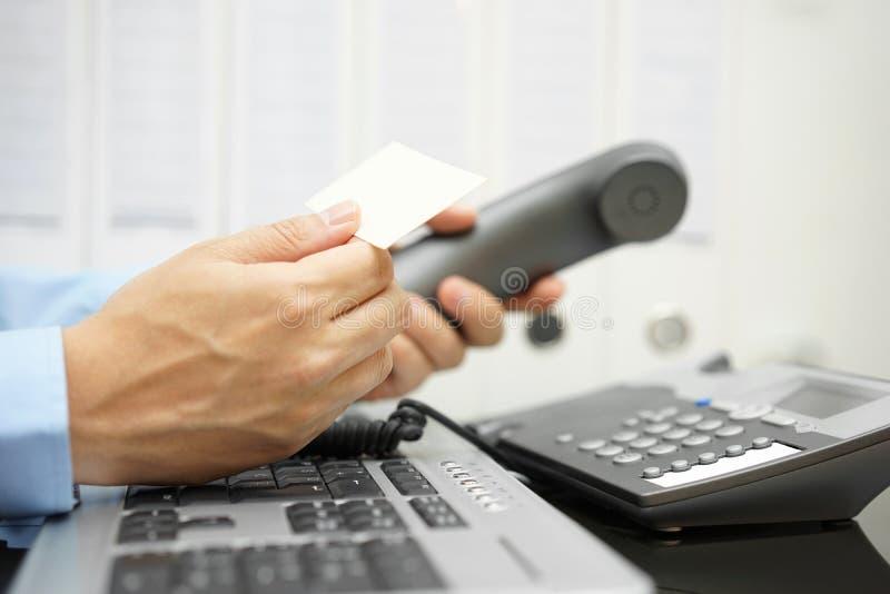 El hombre de negocios sostiene la tarjeta de visita en su mano imagenes de archivo