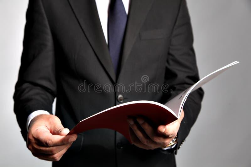 El hombre de negocios sostiene un folleto imagenes de archivo