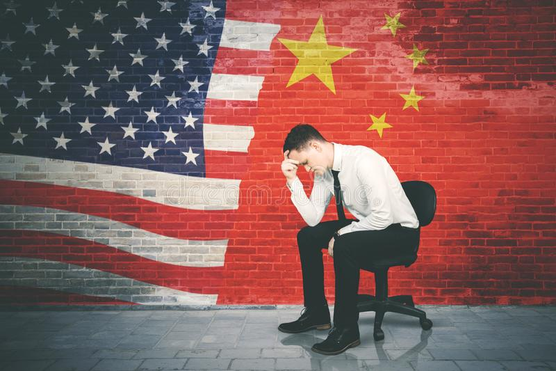 El hombre de negocios subrayado se sienta con la bandera de China y de los E.E.U.U. foto de archivo libre de regalías