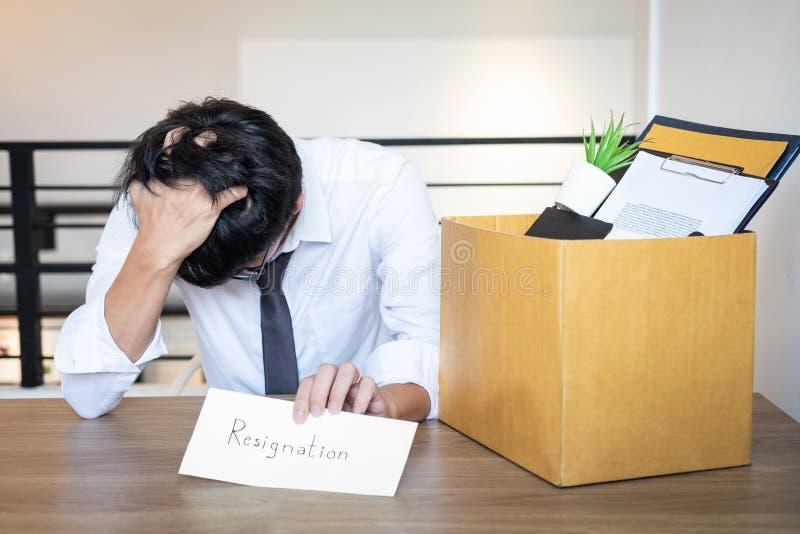 El hombre de negocios subrayado siendo dimisión y compañía y ficheros de las pertenencia que embalan en la caja de cartón marrón, imagen de archivo