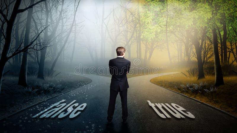 El hombre de negocios tiene que decidir qué dirección es mejor con el ` falso del ` de las palabras y el ` verdadero del ` foto de archivo libre de regalías