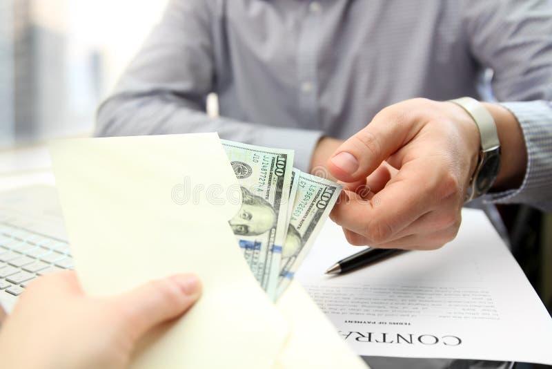 El hombre de negocios toma un soborno durante una firma de un contrato imágenes de archivo libres de regalías