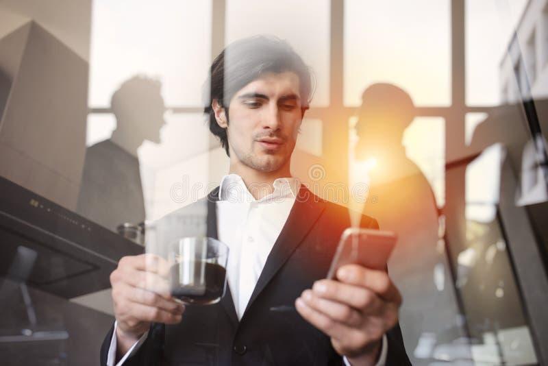 El hombre de negocios trabaja con su smartphone en oficina Exposici?n doble fotografía de archivo libre de regalías