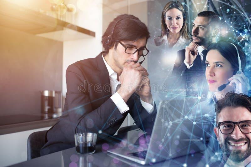 El hombre de negocios trabaja de remoto en casa con sus colegas imagen de archivo
