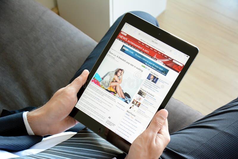 El hombre de negocios usando el aire del ipad, Apple hace tabletas la PC, leyendo noticias de la BBC en línea en sitio web de la  imagenes de archivo