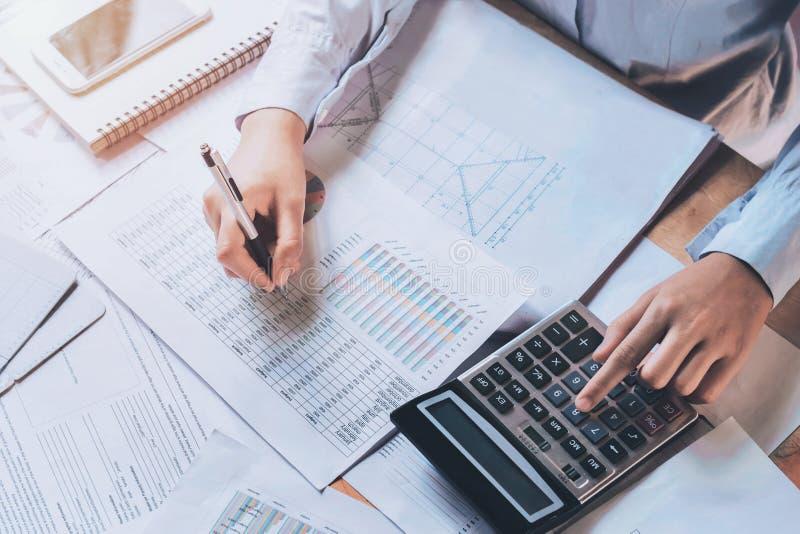 el hombre de negocios usando la calculadora para calcula el presupuesto concepto finan imágenes de archivo libres de regalías