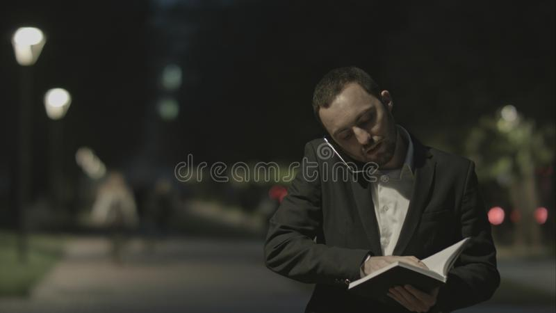 El hombre de negocios usando el teléfono elegante hace una llamada mientras que se coloca en el parque en un cuadrado de ciudad,  imagenes de archivo