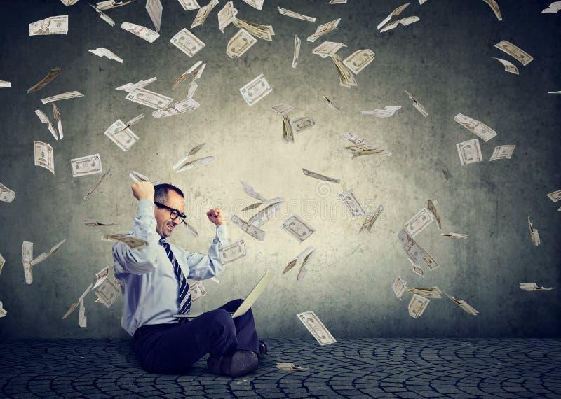 El hombre de negocios usando un ordenador portátil que construye el dinero en línea de la ganancia de negocio bajo billetes de dó fotografía de archivo libre de regalías