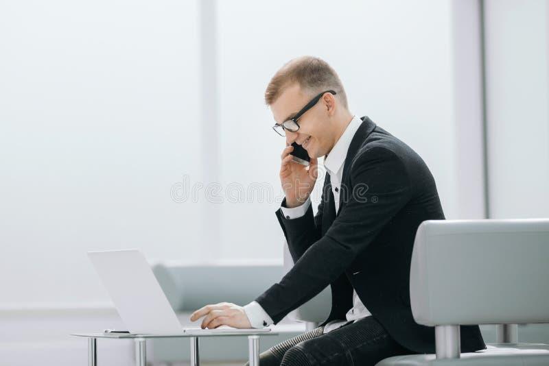 El hombre de negocios utiliza los artilugios que se sientan en el pasillo de la oficina imagenes de archivo