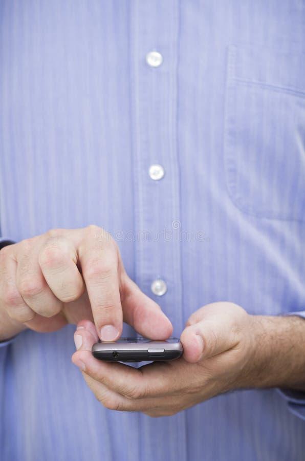El hombre de negocios utiliza un gesto del multi-touch en un smartphon de la pantalla táctil fotos de archivo