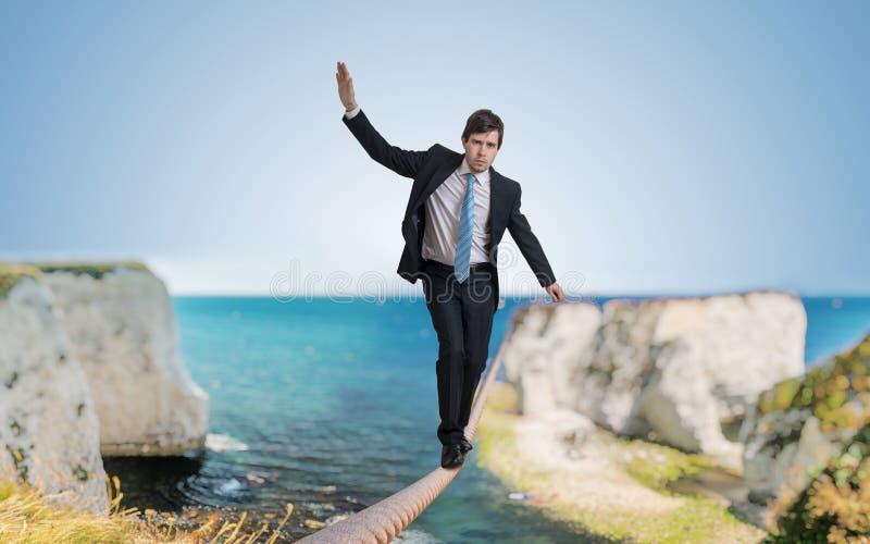 El hombre de negocios valeroso joven está caminando en cuerda foto de archivo libre de regalías