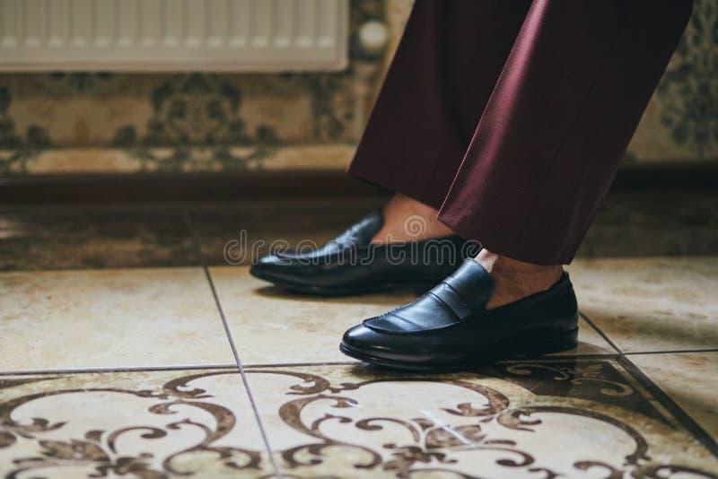 El hombre de negocios viste los zapatos, hombre que consigue listo para el trabajo, mañana del novio antes de la ceremonia de bod imagenes de archivo