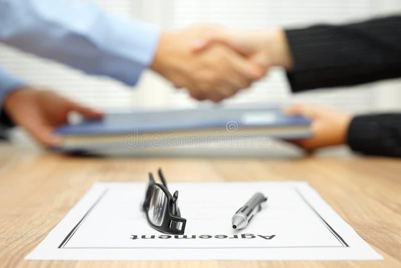 El hombre de negocios y la empresaria están sacudiendo las manos y están intercambiando f imagen de archivo libre de regalías