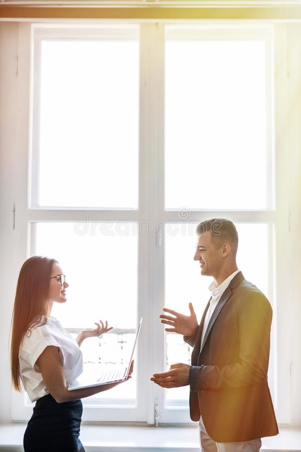 El hombre de negocios y la mujer de negocios discuten informal cerca de las ventanas del edificio de oficinas foto de archivo