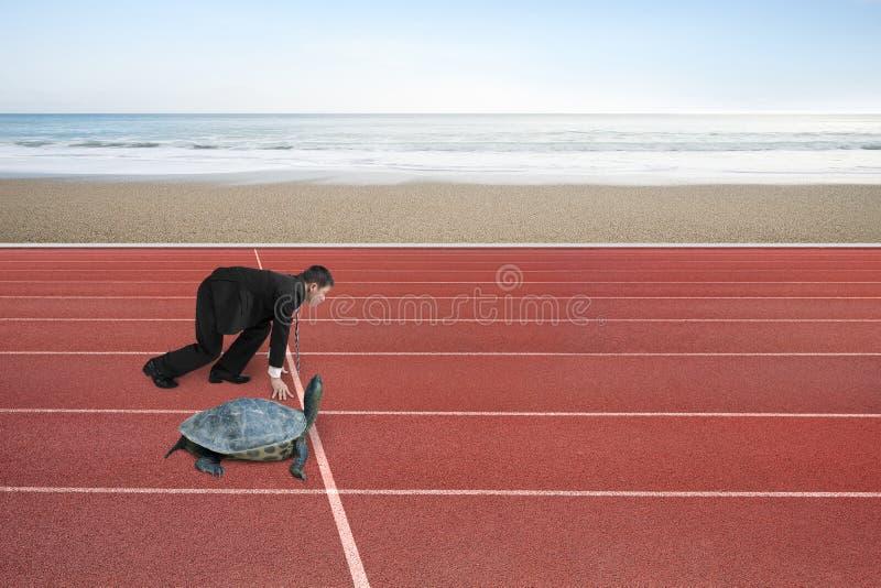 El hombre de negocios y la tortuga están listos para competir con en pista corriente foto de archivo