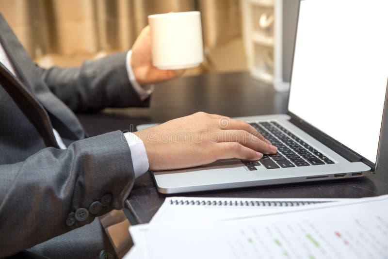 El hombre de Ofticer se sienta en gris del ordenador portátil del uso de la silla en el trabajo de la tabla favorable fotos de archivo
