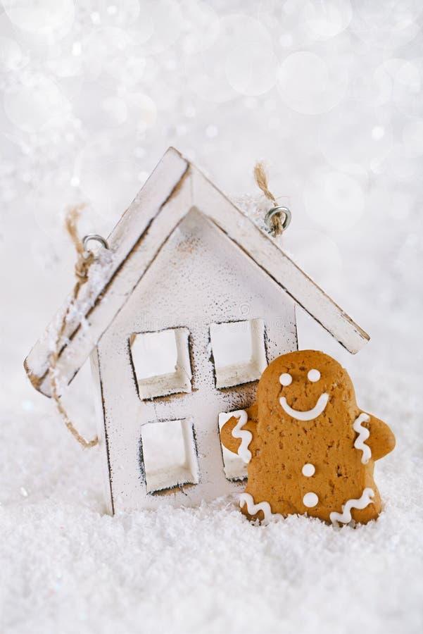 El hombre de pan de jengibre y la casa de madera en una Navidad festiva nievan imagen de archivo