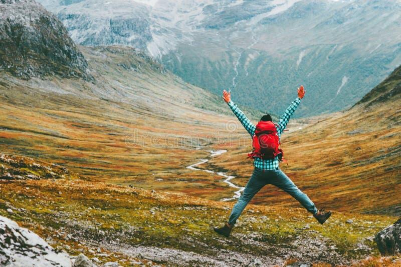 El hombre de salto con la mochila da paisaje aumentado de las montañas foto de archivo