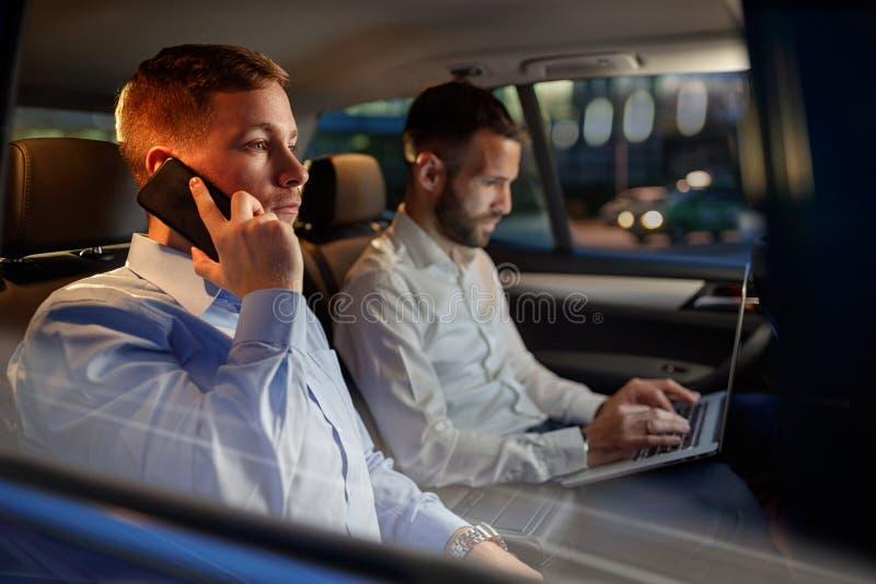 El hombre de trabajo del noche-negocio utiliza smartphone en el coche fotos de archivo libres de regalías