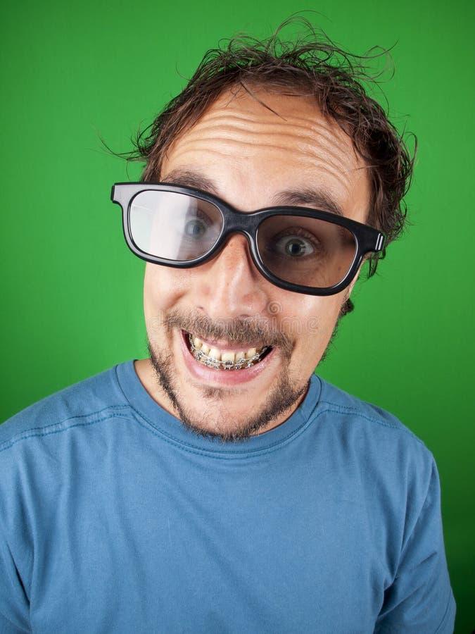 El hombre de treinta años con los vidrios 3d está mirando una película divertida foto de archivo