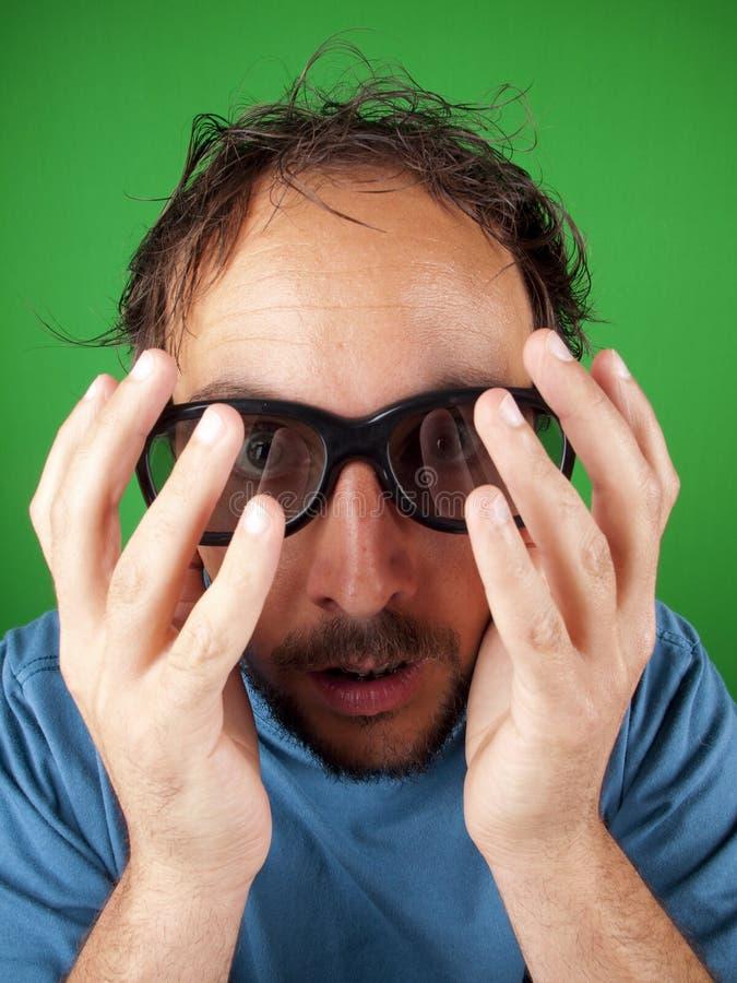 El hombre de treinta años con los vidrios 3d tiene demasiado miedo de mirar foto de archivo libre de regalías