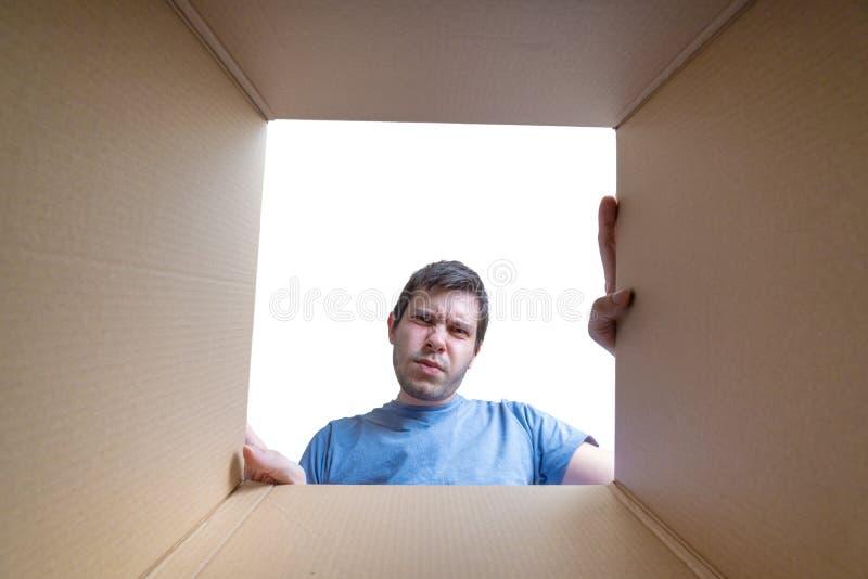 El hombre decepcionado joven está mirando en el regalo dentro de la caja de cartón imagen de archivo libre de regalías