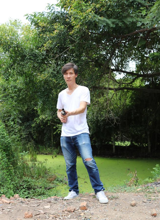El hombre del artillero que coloca el arma largo que apunta el nivel de la cintura con la mezclilla blanca de la camisa y del dri fotografía de archivo libre de regalías